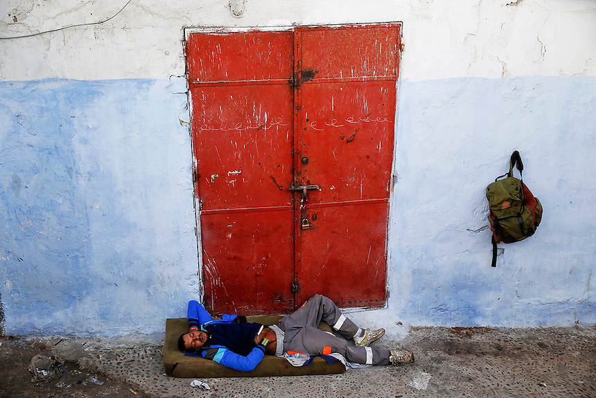 """A man sleeps in front of a closed shop in Rabat's Medina September 23, 2014. Behind walls of Medina and Kasbah of the Oudayas, ancient neighbourhoods of Morocco's capital, labyrinths of small alleys, colourful buildings and street markets offer a glimpse into city's rich history. Rabat was recently listed by UNESCO as a World Heritage Site and suggested as a """"must see"""" destination by major media outlets and tourist agencies.  REUTERS/Damir Sagolj (MOROCCO)"""