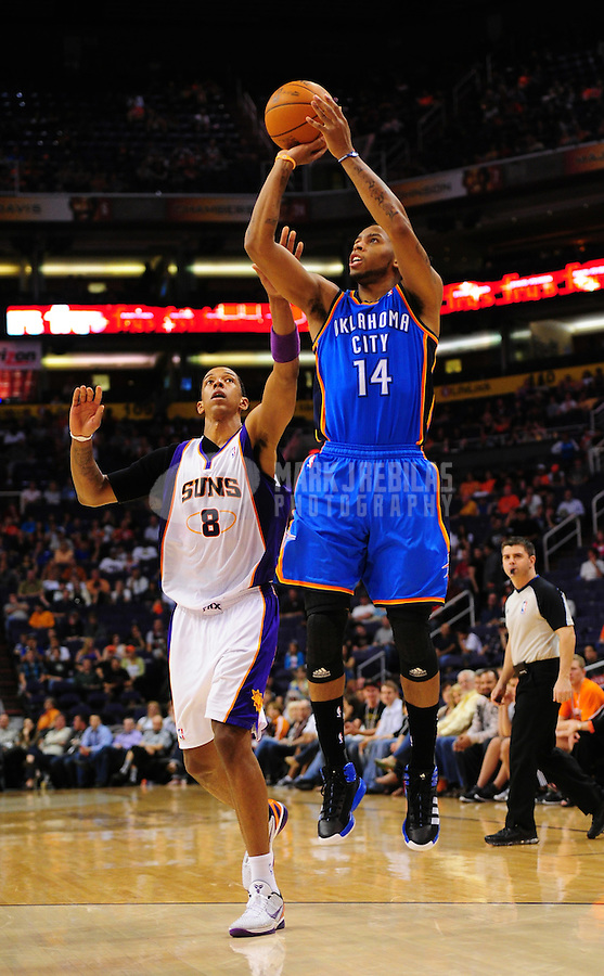 Mar. 30, 2011; Phoenix, AZ, USA; Oklahoma City Thunder guard (14) Daequan Cook controls the ball against Phoenix Suns center (8) Channing Frye at the US Airways Center. Mandatory Credit: Mark J. Rebilas-