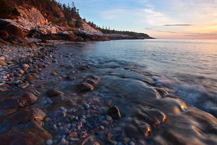Low tide reveals ample off-shore boulders and ephemeral waterfalls as the waves gently roll onto the beach at Duck Harbor in Acadia National Park on Isle au Haut, Maine