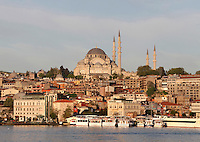 Low angle view of Suleymaniye Mosque or Mosque of Sultan Suleyman the Magnificent (Suleymaniye Camii) 1550-58, by Mimar Sinan, Istanbul, Turkey, at dawn from the Golden Horn. Commissioned by Suleiman the Magnificent, and located on Istanbul's Third Hill, Suleymaniye Mosque was restored in 1665 after a fire, in 1766 due to an earthquake and in 1956 after damage in World War I. The mosque itself is preceded by a monumental courtyard (avlu). At the four corners of the courtyard are the four minarets. The dome is buttressed by two half-domes and two typanum walls. The historical areas of the city were declared a UNESCO World Heritage Site in 1985. Picture by Manuel Cohen.