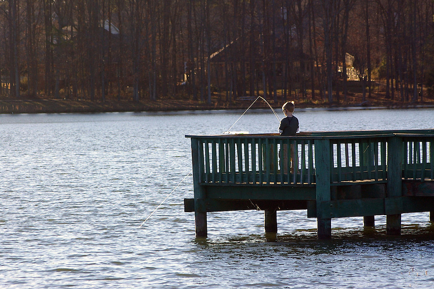 Youngster fishing from a pier on Lake Willastein, Maumelle, Arkansas