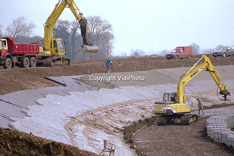 Foto: VidiPhoto..LOENEN - De dijkverzwaring van de Waaldijk tussen Loenen (Gld) en Dodewaard ligt een half jaar achter op schema. Oorzaak zijn de juridische procedures die aannemers tegen elkaar gevoerd hebben. Op dit moment worden er grasbetonblokken aan de buitenzijde van de dijk gelegd, als extra bescherming tegen het hoge water. Sinds de ontwikkeling van de mechanische steenklem is het aantal .rugklachten bij stratenmakers fors afgenomen. Grasbetonblokken wegen ongeveer 45 kilo per stuk.