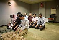 Employees pray near the newsroom at news channel Al Jazeera English in Doha.