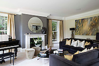 The spacious sitting room is decorated in tones of grey and gold and features a rare antique piano. Two sofas arranged in front of the fireplace provide plenty of comfortable seating and the steel coffee table and circular mirror above the fireplace add a contemporary note to the otherwise traditionally styled room.
