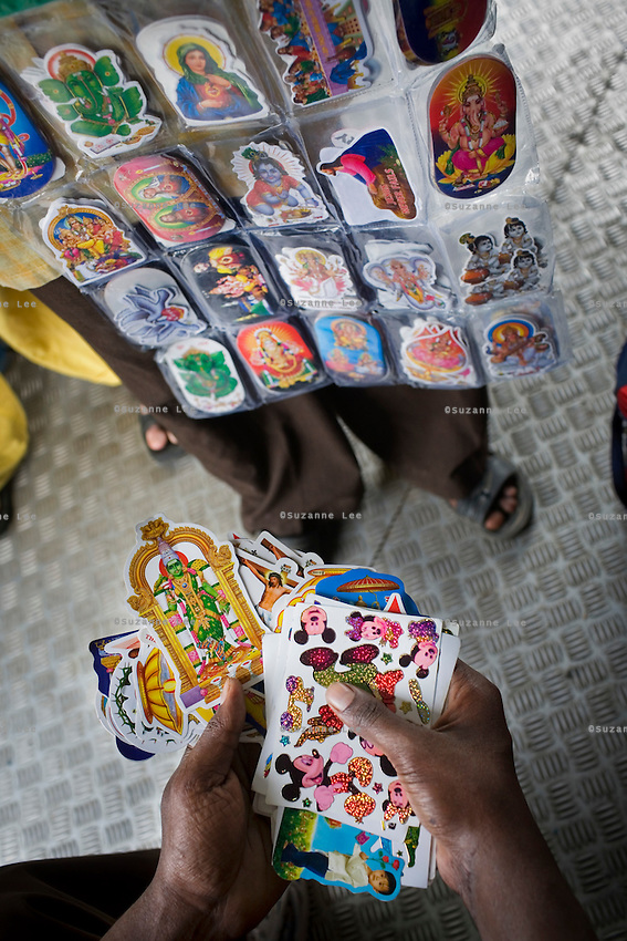 A peddler sells stickers of Mickey Mouse next to an array of Hindu deities and Christian gods on the Himsagar Express 6318 as it passes through Tamil Nadu and Kerala on 9th July 2009.. .6318 / Himsagar Express, India's longest single train journey, spanning 3720 kms, going from the mountains (Hima) to the seas (Sagar), from Jammu and Kashmir state of the Indian Himalayas to Kanyakumari, which is the southern most tip of India...Photo by Suzanne Lee / for The National
