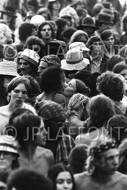 Watkins Glen, NY. July 28th, 1973. <br /> Couple kissing in the middle of the crowd.<br /> The Summer Jam at Watkins Glen was a 1973 rock festival which once received the Guinness Book of World Records entry for &quot;Largest audience at a pop festival.&quot; An estimated 600,000 rock fans came to the Watkins Glen Grand Prix Raceway outside of Watkins Glen, New York on July 28, 1973, to see The Allman Brothers Band, Grateful Dead and The Band perform.<br /> Similar to the 1969 Woodstock Festival, an enormous traffic jam created chaos for those who attempted to make it to the concert site. Long and narrow country roads forced fans to abandon their vehicles and walk 5&ndash;8 miles on that hot summer day. 150,000 tickets were sold for $10 each, but for all the other people it was a free concert. The crowd was so huge that a large part of the audience was not able to see the stage; however, twelve huge sound amplifiers, installed courtesy of legendary promoter Bill Graham, allowed the audience to at least hear.