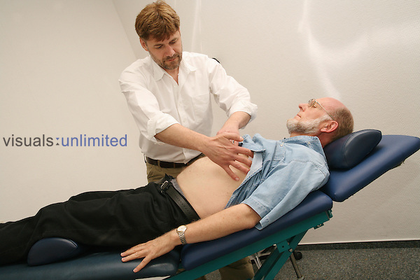 older man getting examinated by a doctor on an examination couch