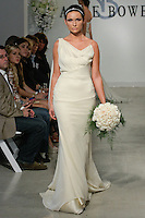 "Model walks runway in a Yorkshirt Bridal gown - champagne georgette gown with draped shoulder detail, from the Anne Bowen Bridal Spring 2013 ""Coat of Arms"" collection fashion show, during Bridal Fashion Week New York April 2012."