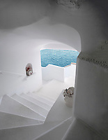 A curved whitewashed staircase descends from the bedrooms towards the swimming pool and the bay of Naples
