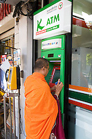 Thailand. Bangkok. Tha Thian . ATM bank machine for a munk from Wat Pho, also known as Wat Phra Chetuphon, or The Temple of the Reclining Buddha, which is a Buddhist temple. Public pay phone in the streets. The cash dispenser is in the window of a 7-Eleven store. 7-Eleven is a worldwide chain of convenience stores.Tha Tian's community is located in the downtown area and in the center of the urban historic district, called Koh Rattanakosin. Tha Thian is surrounded by a major heritage and tourist site, Wat Pho. 31.03.09  © 2009 Didier Ruef