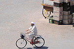 A man on a bike rides through the street in Marrakesh, Morocco.
