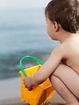 Two year old boy playing with sand at the beach. Sitting with a bucket at the water.