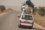 """A """"bush taxi"""" travels the two-lane, international highway from Ouagadougou, Burkina Faso to Niamey, Niger.  The taxi will stop anytime on the side of the road to let passengers on and collect new ones.  The 17-seater vehicle can be stuffed with up to 26 people."""