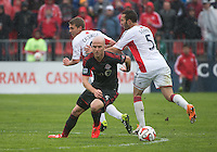Toronto, Ontario - May 3, 2014: Toronto FC midfielder Michael Bradley #4 battles for a ball with New England Revolution midfielder Scott Caldwell #6 and New England Revolution defender A.J. Soares #5 during a game between the New England Revolution and Toronto FC at BMO Field.<br /> The New England Revolution won 2-1.