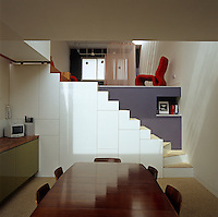 The combined kitchen and dining room plus the living area were planned as one large open-plan room but set on two different levels, with access via a set of shiny white stairs which also hold cupboards