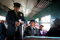 Inspector Juan Lazaro checks passengers tickets. The train has capacity for 320 passengers in four cars.
