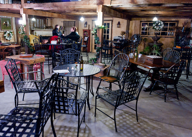 The last few guests linger among the plentifuly tables in the Aspen Dale Winery tasting room at closing time.