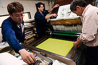 Staff preparing the collotype printing presses. Benrido collotype atelier, Kyoto, Japan, October 9, 2015. The Benrido collotype atelier in Kyoto was founded in 1887 and is the only full-scale commercial collotype atelier in the world. Collotype is a historic photographic printing process that makes use of plates coated in gelatine. It produces prints of unrivalled quality.