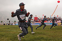 Competitors dressed in PLA (People's Liberation Army) revolutionary era outfits hop in the 'One Legged Race' event at the Red Games. Held in Junan County, this sporting event is a nostalgic tribute to the communist era.