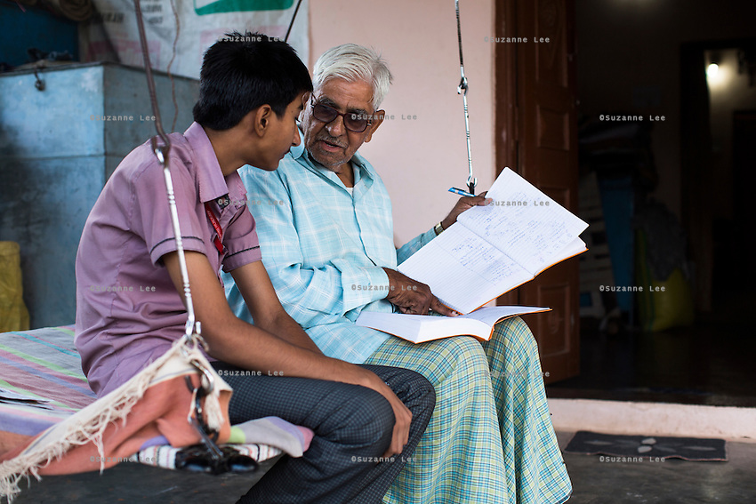 Bhagirata Jat, 72, gives tuition to a teenager in his home in Maheshwar, Khargone, Madhya Pradesh, India on 13 November 2014. Bhagirata is a retired principal of the Fairtrade Premium-funded school Vasudha Vidya Vihar as well as a cotton farmer. The farm has now been handed to his son and grandson who are continuing the farming with Fairtrade. Photo by Suzanne Lee for Fairtrade