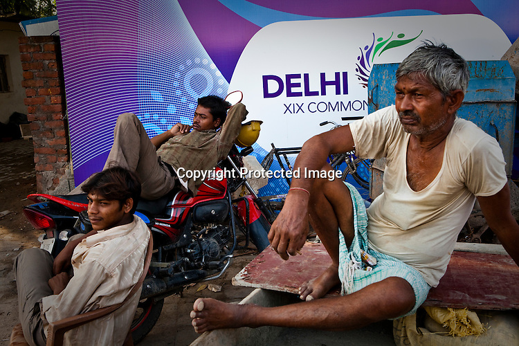 Family members sit outside the Commonwealth Games hoarding that hides their slums in New Delhi, India.