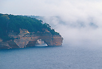Fog rolls in off Lake Superior to obscure the cliffs of Pictured Rocks National Lakeshore near Munising, Mich.