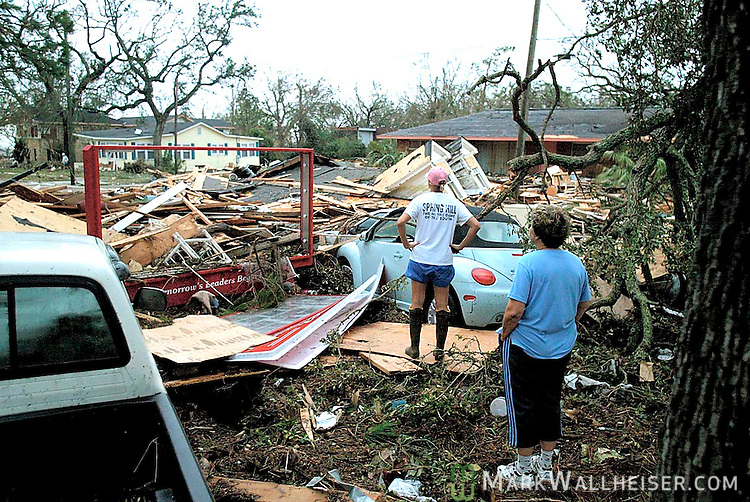 Aerin Gombos (L) and her mother Marie Gombos look over the rubble of the demolished homes of their neighbors in disbelief after Hurricane Katrina moved in on Biloxi August 29, 2005.  The tropical cyclone cause catastrophic damage in Biloxi along the Mississippi Gulf coast.