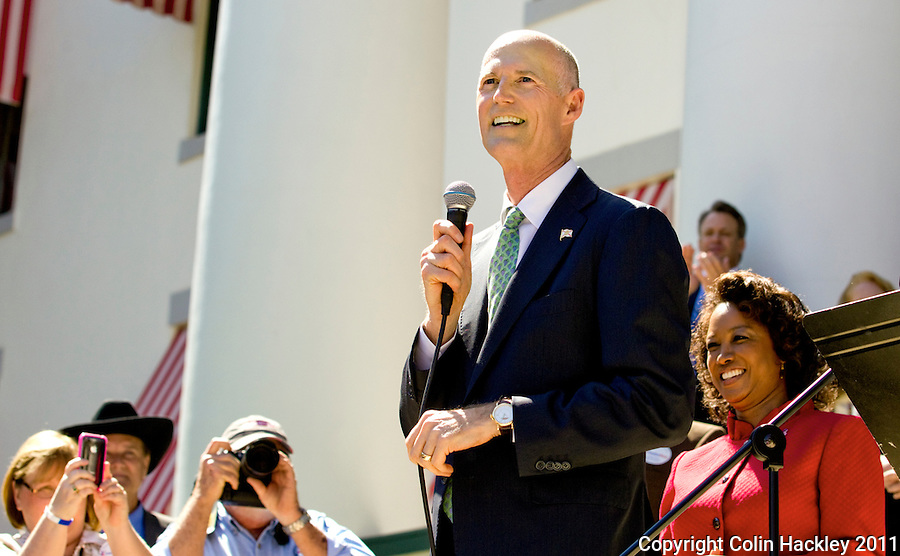 TALLAHASSEE, FLA. 3/8/11-OPENINGDAY030811 CH-Gov. Rick Scott, center, is flanked by Lt. Gov. Jennifer Carroll, right, as he speaks during a Tea Party rally on the opening day of the 2011 legislative session Tuesday at the Capitol in Tallahassee..COLIN HACKLEY PHOTO