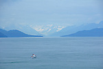 Small boat is dwarfed by the hazy, snowy mountains near the entrance of Glacier Bay National Park, Alaska