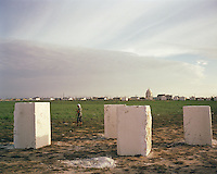 An Uzbek woman walks back to her camp in the Caspian cemetery, to prepare dinner for the grave builders.