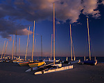 Hobey cats (sailing boats) along Pacific Ocean beach with white clouds and sunset light, Santa Barbara, California USA