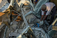 Port Au Prince, Haiti, Jan 24 2010.A man tries to remove the bodies of victims of the earthquake who died when a large concrete block smashed their car..