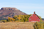 A rock butte rises behind an old red barn on the rolling foothills of the Rocky Mountains.