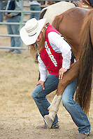 Senior Animal Science major Marissa Wallace, stretches her horse Miley's leg before competing the in the barrel racing portion of Falcon Frontier Days Rodeo at Campus Farm Saturday, September 14, 2013. <br /> Kathy M Helgeson/UWRF Communications