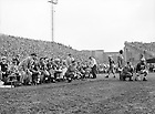 GMCJ 1/23:  Football Game Scene -  Notre Dame vs. Navy, 1949/1029.  Notre Dame bench with Football Coach Frank Leahy (kneeling next to player #55)..Image from the University of Notre Dame Archives.