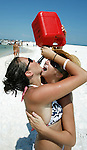 """Lindsey McKendrea (L) and her friend Sissy Mauney, both from Yulee, Florida, drink """"Chirp Chirp"""" from a gasoline can at the 2006 White Trash Bash on Dog Island May 28, 2006, off the coast of Carrabelle, FL.  McKendrea described Chirp Chirp as an upside down margarita.  The White Trash Bash is a yearly boat party at Dog Island, 75 miles south of Tallahassee, Florida, which is a remote island that is only reachable by boat.  This year's party drew thousands in over 350 boats.   (Mark Wallheiser/TallahasseeStock.com)"""