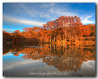 From Pedernales Falls State Park, the last light of day falls across the orange cypress trees in this image taken in mid November. The trees were changing colors, and the water along the river basin in this Texas Hill Country landscape was calm and offered a beautiful reflection.