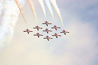 Snowbirds acrobatic team formation in action with smoke on against cloudy sky