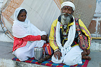 Hindu man and woman with container for holy Ganges water at Dashashwamedh Ghat in Holy City of Varanasi, Benares, India RESERVED USE - NOT FOR DOWNLOAD -  FOR USE CONTACT TIM GRAHAM