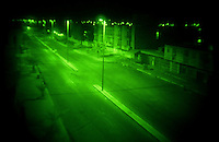 """TIKRIT, IRAQ - AUGUST 7: An infamous stretch of road, known as """"RPG Alley"""" lies vacant on August 7, 2003 in Tikrit, Iraq. A three man scout and sniper team attached to the 1-22 Infantry Brigade patrols the street, often in the dead of night. Dropped off in enemy territory, the team makes their way to an elevated position to observe and possibly fire on any targets along the roadway. (Photo by Benjamin Lowy/Reportage by Getty Images)"""