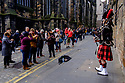 Edinburgh, UK. 15.04.2017. Tourists take snaps of a busking piper on the Royal Mile. Photograph © Jane Hobson.