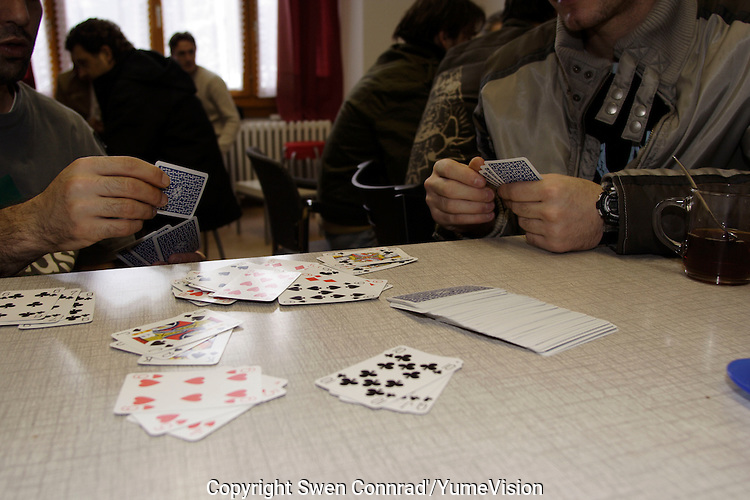 Playing card at the ARAVOH association, 200 meters form the Vallorbe registration Centre of the Federal Office for Refugees (CERA)..The ARAVOH association was open in 2000 by a Christian priest and dozen of volunteers. He offer teas, coffees, biscuits, games, cloths, orientation to other organisations, institutions, associations and a basic psychological support.
