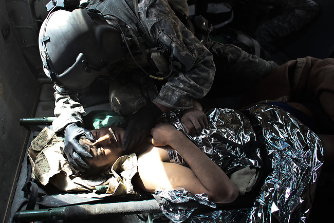 """Sgt. Patrick Schultz, 31, a flight medic with the 101st Combat Aviation Brigade's """"Shadow Dustoff""""  treats an Afghan soldier wounded in a Taliban ambush south of Kandahar, Afghanistan. Sept. 21, 2010. DREW BROWN/STARS AND STRIPES"""