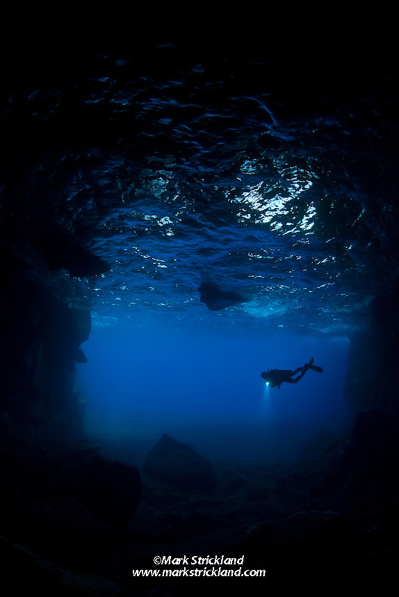 Suspended in clear, blue water, a diver explores the entrance of a large cavern at Barren Island, India's only active volcano. Barren Island, Andaman Islands, India, Andaman Sea