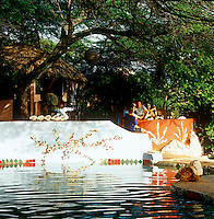 A bar in Jamaica situated under the shade of mature trees with a swimming pool in front