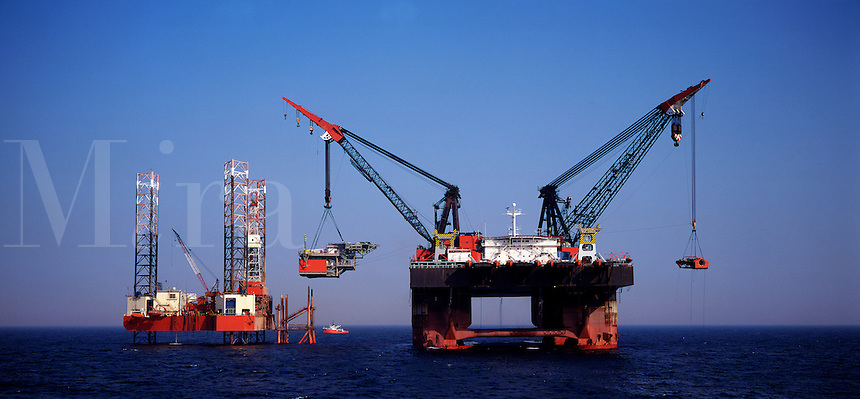 England.  North Sea.  Derrick barge lifting topside of small gas production platform..
