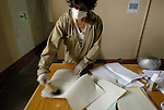 A worker sweeps decades of dust from documents in the Project to Recover the Historical Archives of the National Police of Guatemala, where workers are sorting through and cataloging 80 million pages of records that detail the Central American country's history of repression and violence.