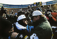 """Carolina Panthers Coach Dom Capers and Green Bay Packers Coach Mike Holmgren meet at mid-field after the Packers defeated the Panthers 30-13 in the NFC Championship game at Lambeau Field on January 12, 1997. This was the first title game in Green Bay since the """"Ice Bowl"""" in 1967."""