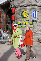 Elderly women walk along the pavement in the Hutongs area, Beijing, China