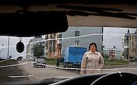 Drab street scene through cracked windshield in remote Soviet town.